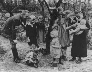 "<p>Nazi policy encouraged racially ""acceptable"" couples to have as many children as possible. Because of the number of children in this Nazi Party official's family, the mother earned the ""Mother's Cross."" Germany, date uncertain.</p>"