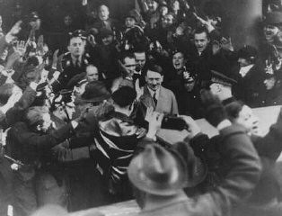 <p>Germans cheer Adolf Hitler as he leaves the Hotel Kaiserhof just after being sworn in as chancellor. Berlin, Germany, January 30, 1933.</p>
