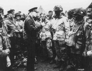 """<p>General Dwight D. Eisenhower visits with paratroopers of the 101st Airborne Division just hours before their jump into German-occupied France (<a href=""""/narrative/2899/en"""">D-Day</a>). June 5, 1944.</p>"""