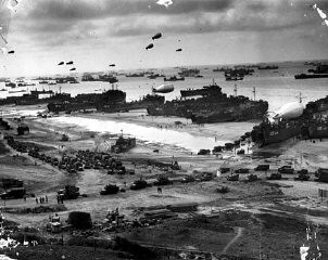 "<p>The Normandy beach as it appeared after <a href=""/narrative/2899/en"">D-Day</a>. Landing craft on the beach unload troops and supplies transferred from transports offshore. Barrage balloons hover overhead to deter German aircraft. Normandy, France, undated (after June 6, 1944).</p>"
