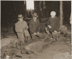 "<p>Three German mayors view the corpse of a prisoner burned alive in a barn by the SS while on a death march from Rottleberode, a subcamp of Dora-Mittelbau. <a href=""/narrative/8101/en"">Gardelegen</a>, Germany, April 18, 1945.</p>"
