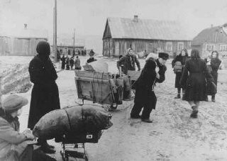 "<p>Jews forced into the <a href=""/narrative/3182/en"">Kovno</a> ghetto move their belongings into the ghetto. In the center, a man is pulling a disassembled wardrobe. He was never able to put it together because of the crowded conditions in the ghetto. Clothes were often hung from nails in the wall instead. Lithuania, ca. 1941-1942.</p>"