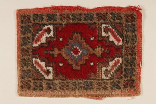 <p>This small patterned hooked rug was used as a shoe mat in the wagon of Rita Prigmore and her family when she was a child in Wurzberg, Germany, after World War II.Rita and her family were members of the Sinti group of Roma (Gypsies). She and her twin sister Rolanda were born in 1943. Rolanda died as a result of medical experiments on twins in the clinic where they were born. Rita was returned to her family in 1944. She and her mother survived the war and moved to the United States, before returning to Germany to run a Sinti human rights organization that sought to raise consciousness about the fate of Roma during the Holocaust.</p>