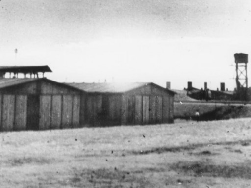 """<p>View of the <a href=""""/narrative/10797/en"""">Trawniki</a> training camp showing two barracks and a watch tower. Trawniki, Poland, between 1941 and 1944.</p>"""