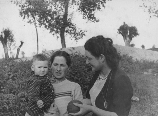 """<p>Hinda Eidenberg (center) stands outdoors in a field with her child and her niece. Pictured from right to left are: Sabina Weinstock (Hinda's niece), Hinda Eidenberg, and Hinda's child. Hinda and her child later perished in the <a href=""""/narrative/10797/en"""">Trawniki</a> camp. Photograph taken inKozienice, Poland, 1940.</p>"""