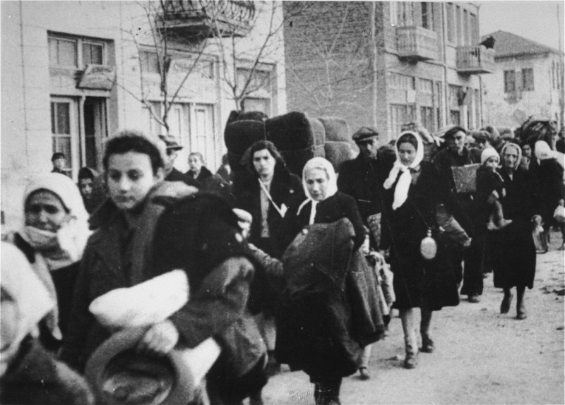 Jewish deportees from Macedonia march along a street in Skopje carrying their belongings. Skopje, [Macedonia] Yugoslavia, March 1943.   The Jews of Bulgarian-occupied Thrace and Macedonia were deported in March 1943. Between March 4 and March 9, the 4,219 Jews from Thrace were rounded-up and concentrated in the two towns of Gorna Dzumaya and Dupnitsa. Two weeks later, between March 19 and March 21, they were transported in two trains to the port of Lom on the Danube. From Lom they were loaded onto four Bulgarian ships and taken to Vienna, where they were once again put on trains bound for Treblinka. On March 11, over 7,000 Macedonian Jews from Skopje, Bitola, and Stip were also rounded-up and assembled at the Tobacco Monopoly in Skopje, whose several buildings had been hastily converted into a transit camp. The Macedonian Jews were kept there between eleven and eighteen days, before being deported by train in three transports between March 22 and 29, to Treblinka. None of those deported from the Tobacco Monopoly survived.