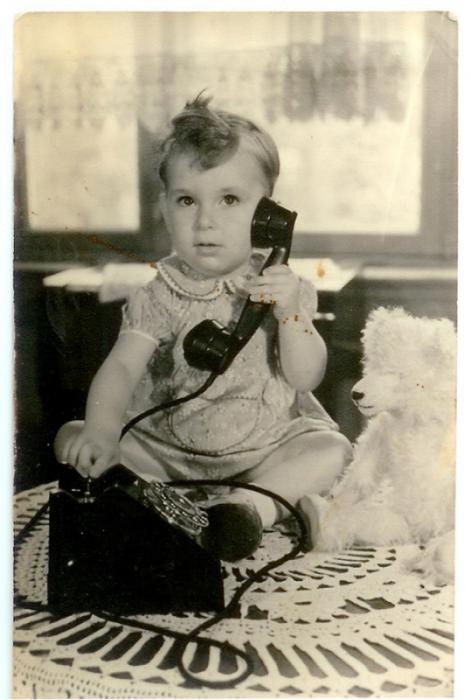<p>Robert Coopman was born in the Netherlands in September 1940.  This 1941 photograph shows Robert holding a telephone while sitting next to a teddy bear. He and his parents lived in Amsterdam where his father was a salesman and bookkeeper. </p>