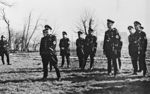 <p>Scene during a visit by SS officer Theodor Eicke to the Lichtenburg camp in March 1936.</p> <p>Lichtenburg was one of the first concentration camps established in Germany were established soon after Hitler's appointment as chancellor in January 1933.</p> <p>When SS chief leader Heinrich Himmler centralized the administration of the concentration camps and formalized the camp system, he chose SS Lieutenant General Theodor Eicke for the task. Himmler appointed him Inspector of Concentration Camps, a new section of the SS subordinate to the SS Main Office.Eicke had been the commandant of the concentration camp at Dachau since June 1933.</p>