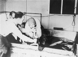 """<p>A victim of a <a href=""""/narrative/3000/en"""">Nazi medical experiment</a> is immersed in icy water at the <a href=""""/narrative/4391/en"""">Dachau</a> concentration camp. SS doctor Sigmund Rascher oversees the experiment. Germany, 1942.</p>"""