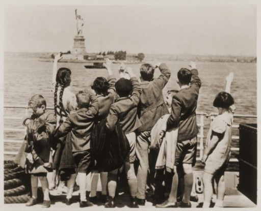 Jewish refugee children wave at the Statue of Liberty as the President Harding steams into New York harbor.