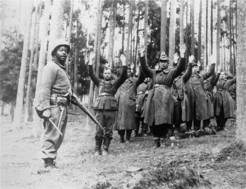 An African-American soldier with the 12th Armored Division, Seventh U.S. Army, stands guard over a group of German soldiers captured in the forest. Germany, 1945.