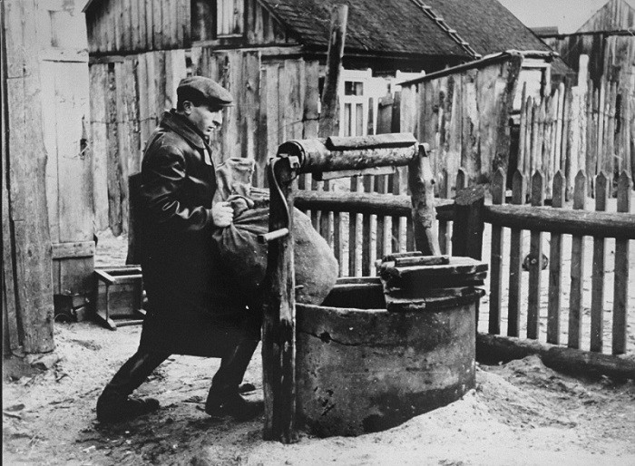 """<p>Photograph taken by <a href=""""/narrative/11692/en"""">George Kadish</a>: a member of the Kovno ghetto underground hides supplies in a well used as the entrance to a hiding place in the ghetto. Kovno, Lithuania, 1942.</p>"""