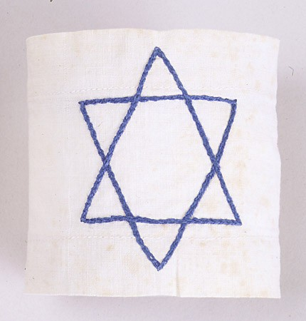 <p>White armband with a Star of David embroidered in blue thread, worn by Dina Offman from 1939 until 1941 while in the ghetto in Stopnica, Poland.</p>
