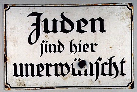"""<p>Signs excluding Jews, such as the sign shown here, were posted in public places (including parks, theaters, movie houses, and restaurants) throughout Nazi Germany. This sign states in German: """"Jews are not wanted here.""""</p>"""