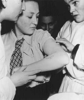 A former concentration camp prisoner receives care from a mobile medical unit of the United Nations Relief and Rehabilitation Administration.