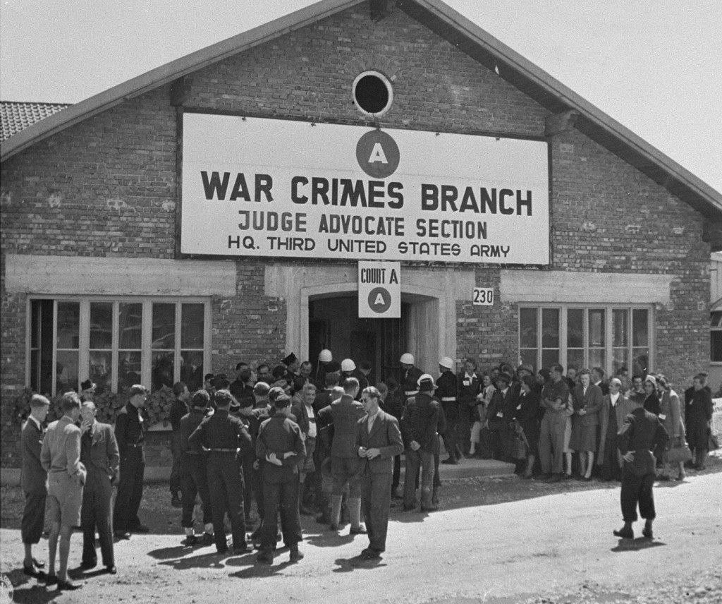 """<p>A crowd waits outside the American military court for the announcement of a verdict in the <a href=""""/narrative/24610/en"""">Malmedy</a> war crimes trial of SS soldiers accused of taking part in the massacre of American prisoners of war. Dachau, Germany, July 16, 1946.</p>"""