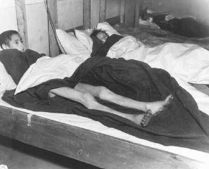 """<p>Two emaciated female Jewish survivors of a death march lie in an American military field hospital in Volary, Czechoslovakia.Pictured on the left is seventeen-year-old Nadzi Rypsztajn.<br /><br />The original caption reads """"This girl, only seventeen years old, was forced to march 18 miles a day for 30 days on one bowl of soup a day. The 5th Infantry Division of the U.S. Third Army found 150 in the same condition when they entered Volary, Czechoslovakia.""""</p>"""