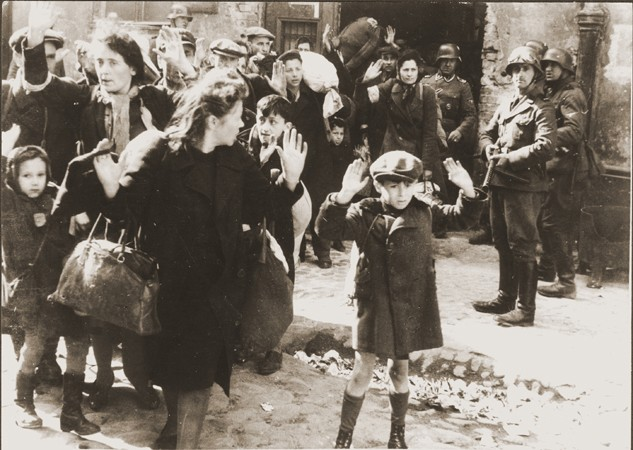 """<p>Jews captured by German troops during the <a href=""""/narrative/3636/en"""">Warsaw ghetto uprising</a> in April–May 1943. This photograph appeared in the <a href=""""/narrative/2012/en"""">Stroop Report</a>, an album compiled by SS Major General Juergen Stroop, commander of German forces that suppressed the Warsaw ghetto uprising. The album was introduced as evidence at the <a href=""""/narrative/9366/en"""">International Military Tribunal</a> at Nuremberg. In the decades since the trial this photo has become one of the iconographic images of the Holocaust.</p>"""