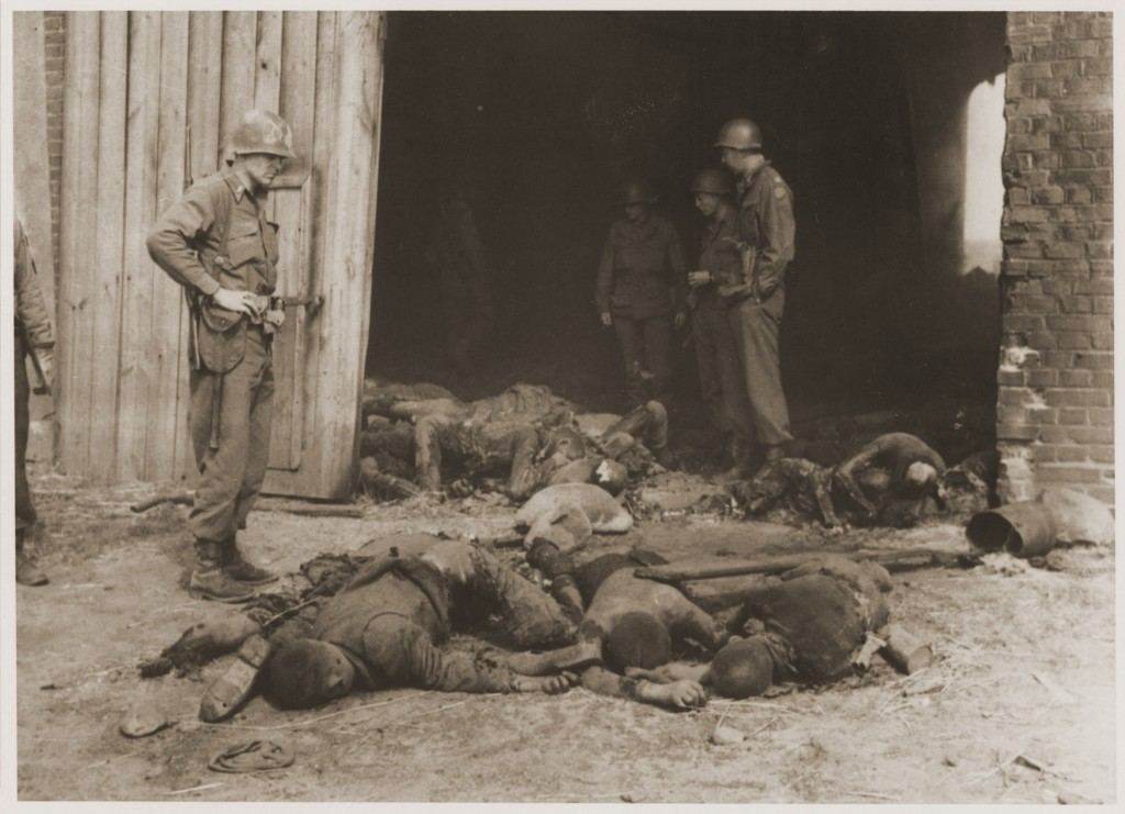American soldiers stand among the bodies of prisoners killed by the SS in a barn outside the town of Gardelegen.