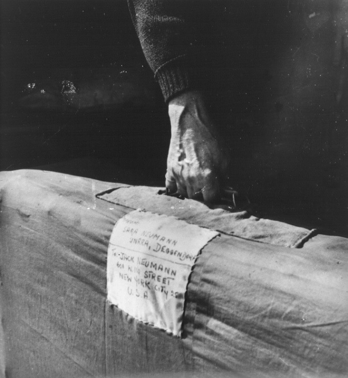 Sara Neumann carries her luggage labled with an address in New York as she leaves the Deggendorf displaced persons camp.