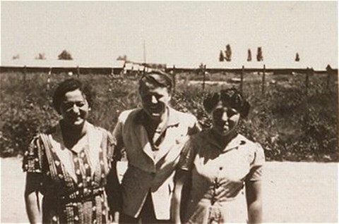 """<p>A woman (right) imprisoned in the <a href=""""/narrative/4842"""">Gurs</a> camp stands with two Quaker delegates who worked for the <a href=""""/narrative/4339"""">American Friends Service Committee</a>. Gurs, France, after January 1941.</p>"""