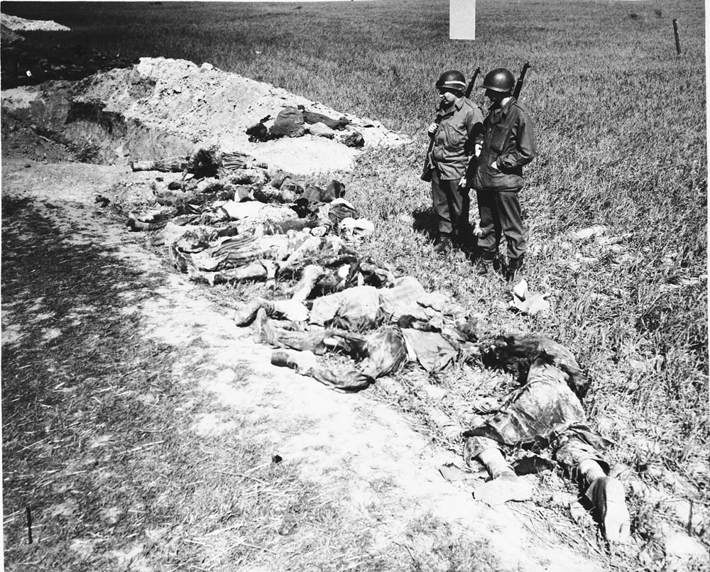 """<p>American soldiers look at the exhumed bodies of prisoners who were burned alive in a barn outside <a href=""""/narrative/8101"""">Gardelegen</a>. Germany, April 14-18, 1945.</p>"""