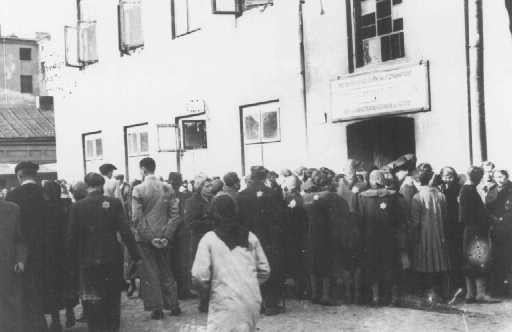 Jews in the Lodz ghetto line up outside the labor office of the Jewish council in the hopes of finding employment outside the ghetto. [LCID: 80561]