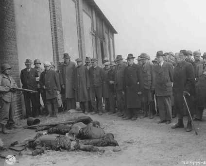 "<p>A US soldier stands guard as mayors and citizens of local towns view the corpses of inmates of the Rottleberode subcamp of Dora-Mittelbau, who were killed when the SS locked them in a barn and set it on fire. <a href=""/narrative/8101"">Gardelegen</a>, Germany, April 18, 1945.</p>"