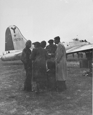 """<p><a href=""""/narrative/27908"""">Haviva Reik</a> and other <a href=""""/narrative/5666"""">parachutists from Palestine</a>, under British command, sent to <a href=""""/narrative/10724"""">Slovakia</a> to aid Jews during the Slovak national uprising. Hayim Hermesh (left), Haviva Reik (second from left), Rafi Reiss (behind Reik), Abba Berdichev (second from the right), and Zvi Ben-Yaakov (right), on the Tri Duby airfield before being sent to Slovakia. Czechoslovakia, September 1944.</p>"""