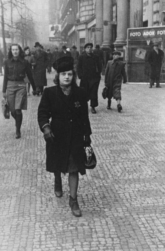 Elsa Eisner, marked with a Jewish badge, walks down a street in Prague. [LCID: 04570]