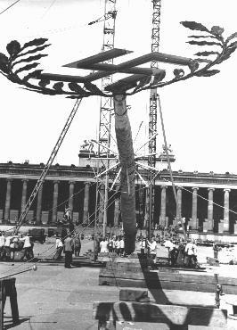 <p>Sebuah tiang berhiaskan untaian bunga (maypole) dengan swastika di puncaknya didirikan untuk parade Hari Buruh di Lustgarten, Berlin. Hari Buruh merupakan perayaan penting dalam kalender Nazi. Jerman, 26 April 1939.</p>