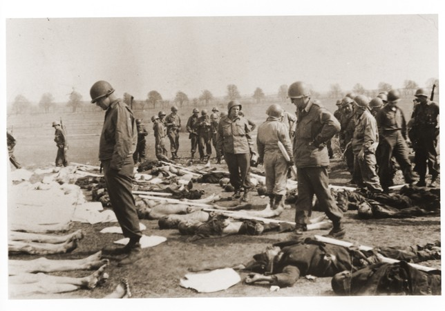 American soldiers view the bodies of prisoners laid out in rows in an open field at Ohrdruf, a subcamp of Buchenwald in Germany.