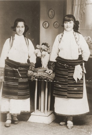 """<p>Portrait of two Jewish girls dressed in traditional Macedonian costume in a private home in Bitola. Pictured are Matilda Kamchi (or Camhi, left) and a friend. Both perished in <a href=""""/narrative/3819"""">Treblinka</a>. Bitola, 1937.</p>"""