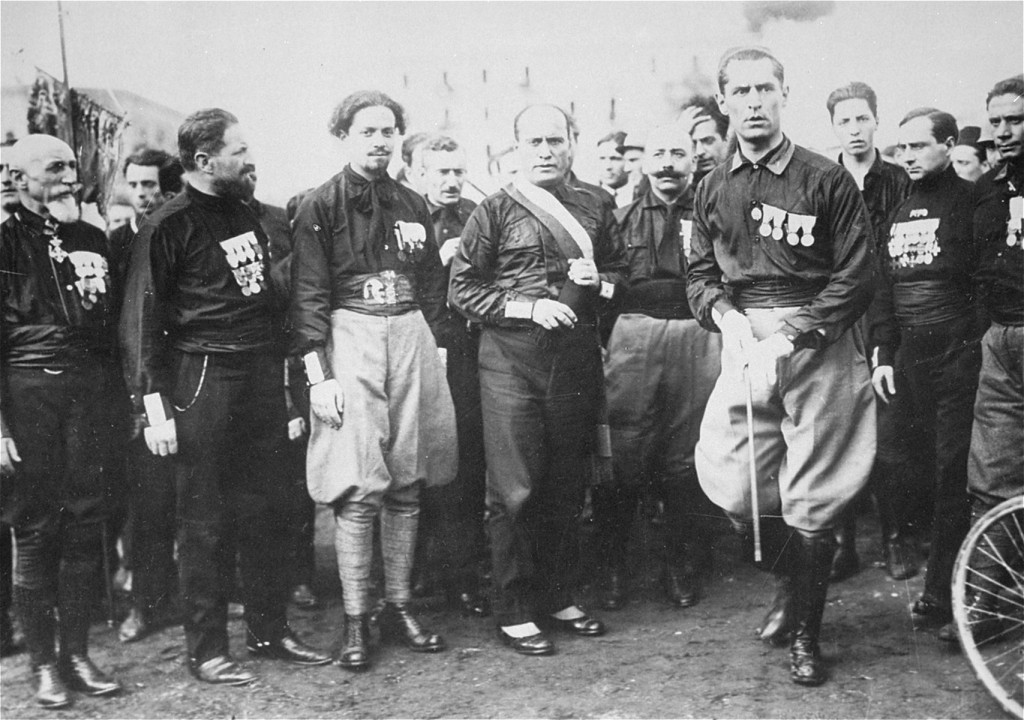 <p>Italian Fascist leader Benito Mussolini (center) with aides and supporters. They are wearing the attire which gave them the name of <em>blackshirts</em>. Italy, 1920s.</p>