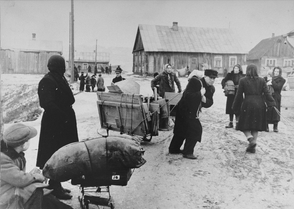 "<p>Jews forced into the <a href=""/narrative/3182"">Kovno</a> ghetto move their belongings into the ghetto. In the center, a man is pulling a disassembled wardrobe. He was never able to put it together because of the crowded conditions in the ghetto. Clothes were often hung from nails in the wall instead. Lithuania, ca. 1941-1942.</p>"