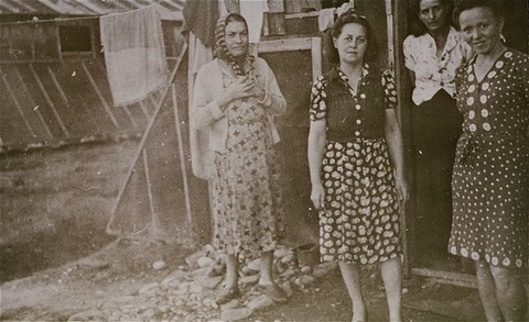 Women prisoners standing in front of barracks at the Gurs camp. [LCID: 03423]