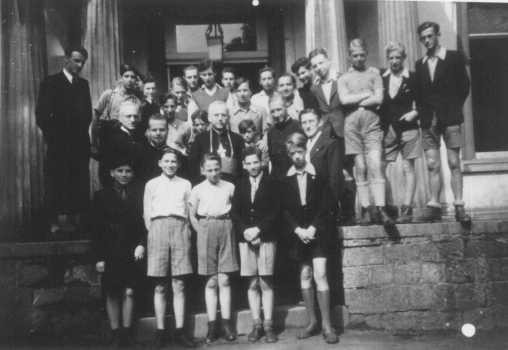 <p>The Bishop of Namur visits a Catholic home for boys, where ten or more of the boys were known to be Jewish. Dinant, Belgium, March-June 1944.</p>