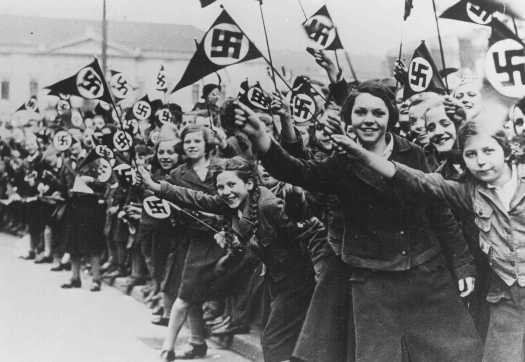 Members of the League of German Girls wave Nazi flags in support of the German annexation of Austria. [LCID: 78546]