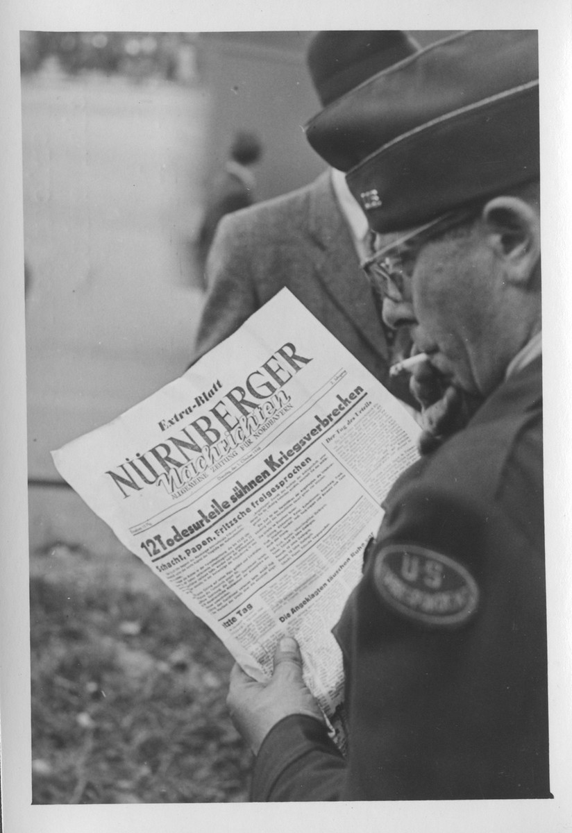 """<p>An American correspondent reads a special edition of the <em>Nürnberger</em> newspaper reporting the sentences handed down by the <a href=""""/narrative/9366"""">International Military Tribunal</a>. Nuremberg, Germany, October 1, 1946.</p>"""
