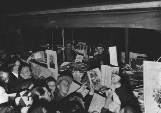 """<p>Germans crowd around a truck filled with """"un-German"""" books, confiscated from the library of the Institute for Sexual Science, for burning by the Nazis. The books were publically burned at Berlin's Opernplatz (Opera Square). Berlin, Germany, May 10, 1933.</p>"""