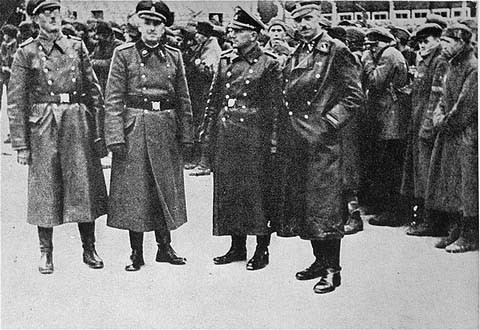 SS officers posing in front of a newly arrived transport of Soviet prisoners of war. [LCID: 19482]