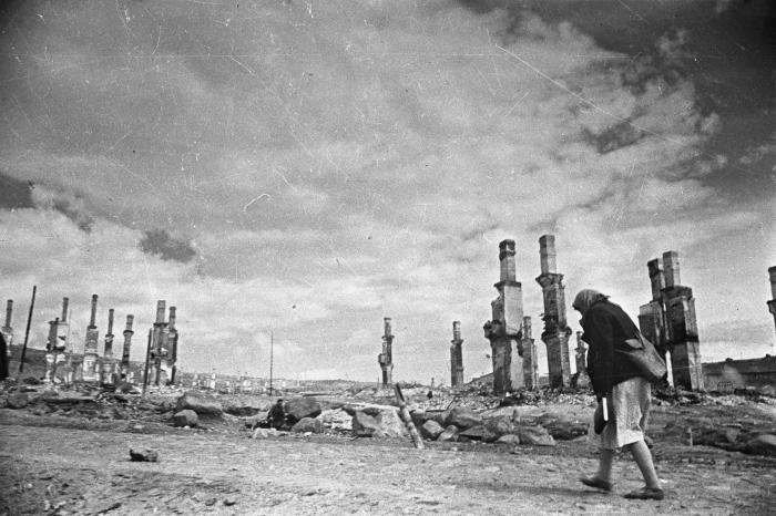 """<p><span style=""""font-weight: 400;"""">A woman walks along a road past a line of chimneys in the destroyed city of Murmansk. Photograph taken by Soviet photographer</span><span style=""""font-weight: 400;"""">Yevgeny Khaldei. Murmansk, Soviet Union, June 1941.</span></p>"""