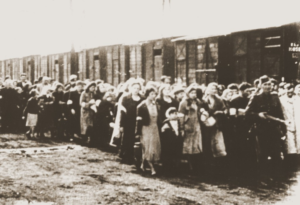 Jews being deported from the Warsaw ghetto march to the freight trains. [LCID: 05554]