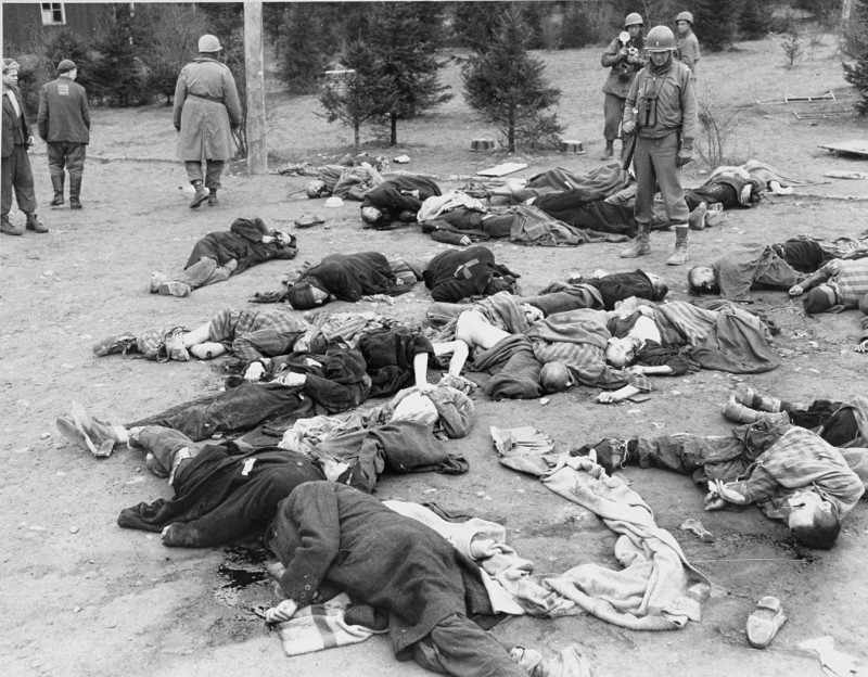 """<p>US soldiers of the <a href=""""/narrative/7807/en"""">4th Armored Division</a> survey the dead at <a href=""""/narrative/7757/en"""">Ohrdruf</a>, a subcamp of the <a href=""""/narrative/3956/en"""">Buchenwald</a> concentration camp. Germany, April 1945.</p>"""