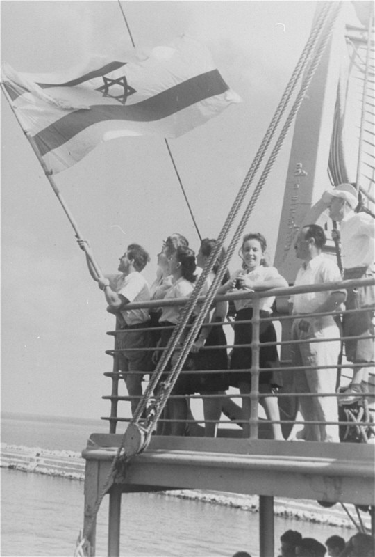 "<p>Jewish refugee children unfurl the Zionist flag as they arrive at the Haifa port aboard <a href=""/narrative/7475"">Aliyah Bet</a> (""illegal"" immigration) ship SS <em>Franconia</em>. Palestine, September 1945.</p>"