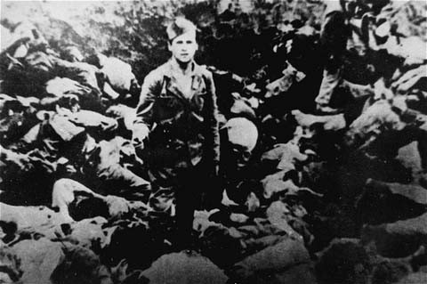 A Ustasa (Croatian fascist) guard stands amid corpses at the Jasenovac concentration camp, Yugoslavia, 1942. [LCID: 64309]