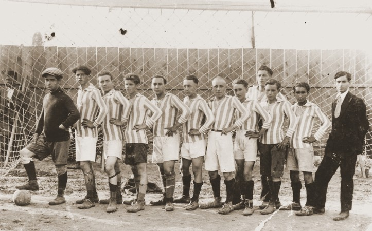 Members of a soccer team in Bitola pose in the goal of a sports field. [LCID: 97811]