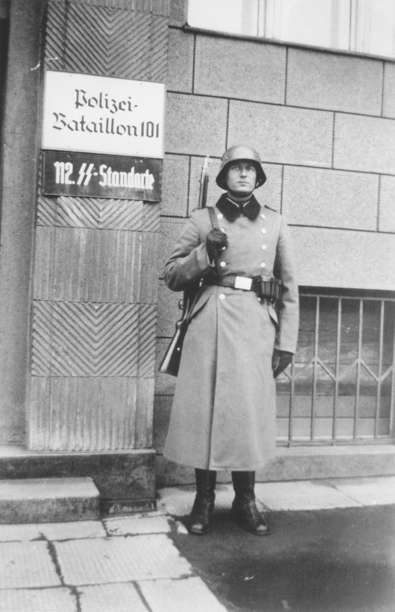 """<p>Bernhardt Colberg, a member of Reserve Police Battalion 101, poses in front of its headquarters in the vicinity of <a href=""""/narrative/2152"""">Lodz</a> in German-occupied <a href=""""/narrative/2103"""">Poland</a>. The police battalions were units of the German Order Police who were deployed to German-occupied areas of Europe during <a href=""""/narrative/2388"""">World War II</a>. Photo dated 1940–1941.</p>"""