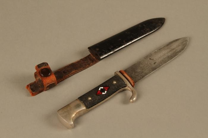 """<p><span style=""""font-weight: 400;"""">This <a href=""""/narrative/52091"""">Hitler Youth</a> knife and case is shaped like a military bayonet and bears the emblem of the Hitler Youth.</span></p> <p><span style=""""font-weight: 400;"""">Beginning in 1933, the Hitler Youth and the League of German Girls had an important role to play in the new <a href=""""/narrative/2529"""">Nazi regime</a>. Through these organizations, the Nazi regime planned to <a href=""""/narrative/11357"""">indoctrinate young people</a> with Nazi ideology. This was part of the process of Nazifying German society. The aim of this process was to dismantle existing social structures and traditions. The Nazi youth groups were about imposing conformity. Youth throughout Germany wore the same uniforms, sang the same Nazi songs, and participated in similar activities. Knives such as this one emphasize the paramilitary nature of the Hitler Youth organization. It was designed to train boys as future fighters and soldiers for the Nazi cause.</span></p> <p><span style=""""font-weight: 400;"""">These items were found in a warehouse in Aachen, Germany, by US Army soldier Sidney Conners in July 1944.</span></p>"""