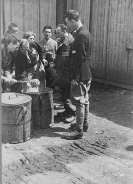 <p>Prisoner forced laborers crowd around containers of food. Plaszow labor camp, Poland, 1943-1944.</p>